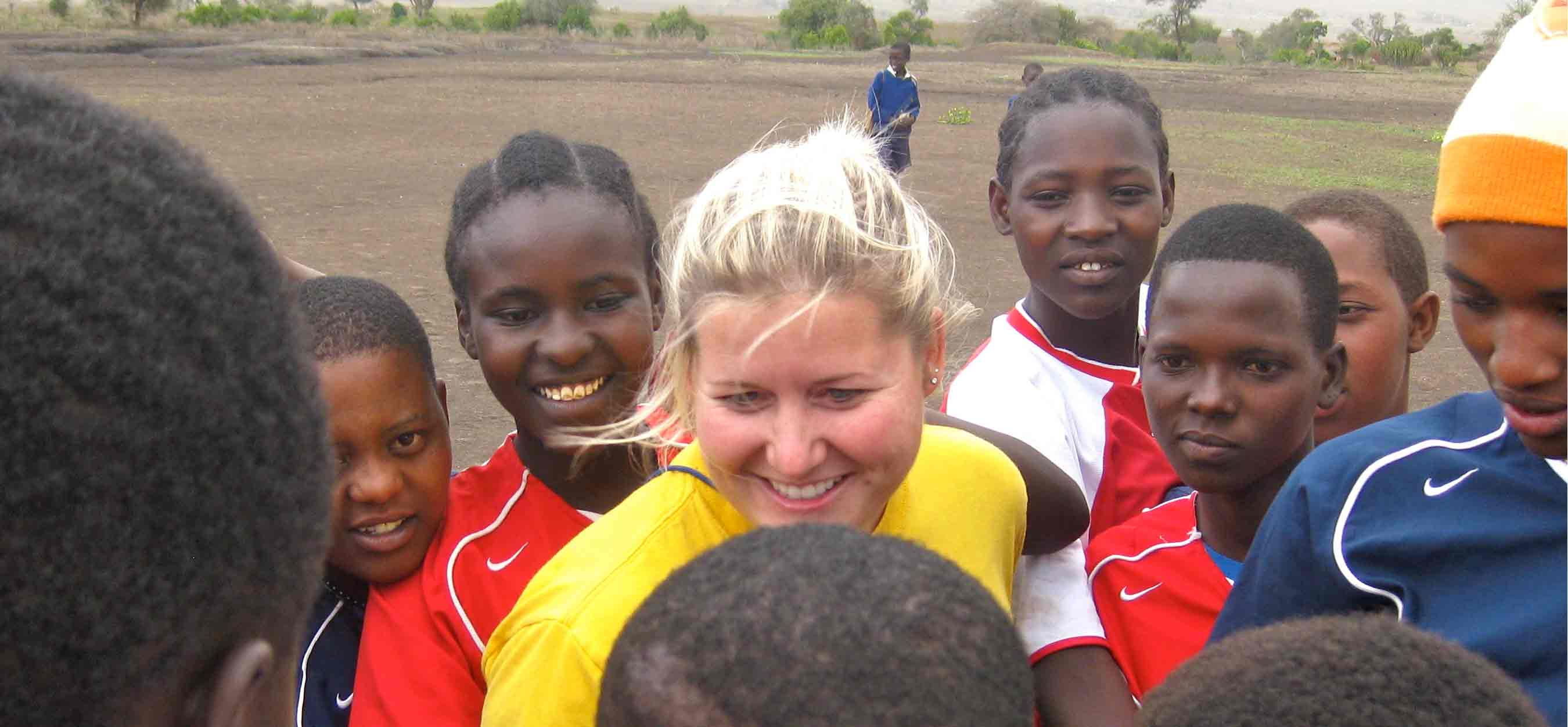 Ashley playing soccer with kids in the village